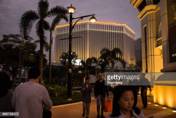 Pedestrians walk past the Venetian Macao resort and casino operated by Sands China Ltd a unit of Las Vegas Sands Corp illuminated at night in Macau...