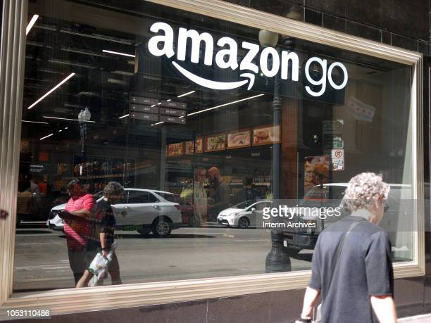 Pedestrians walk past the window of the newly opened Amazon Go store located at 144 South Clark Street in Chicago Illinois October 2018