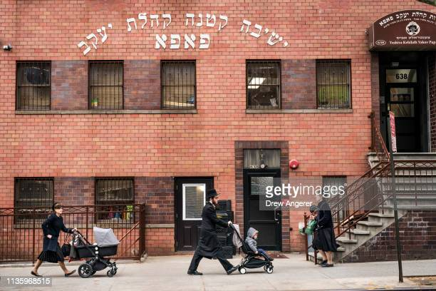 Pedestrians walk past the Yeshiva Kehilath Yakov School in the South Williamsburg neighborhood April 9 2019 in the Brooklyn borough of New York City...