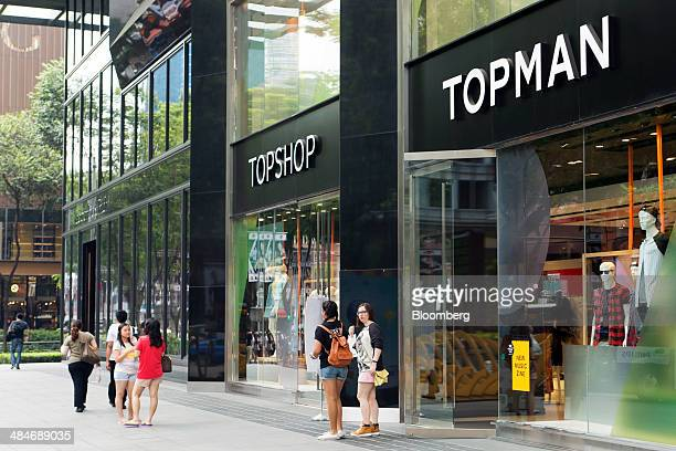 Pedestrians walk past Topshop left and Topman stores both operated by Arcadia Group Plc on Orchard Road in Singapore on Friday April 11 2014...