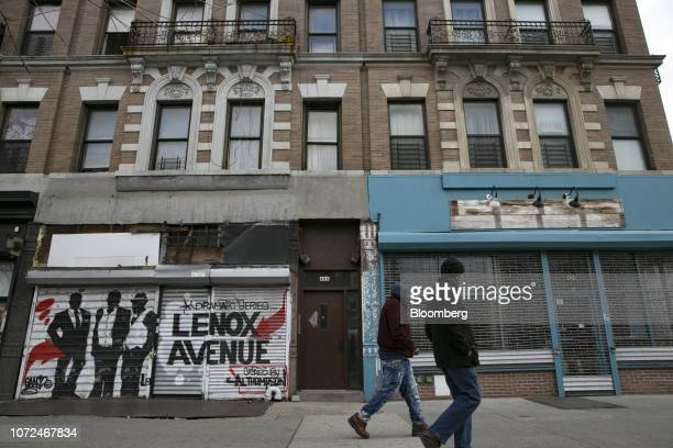 Pedestrians walk past vacant storefronts in the East Harlem neighborhood of New York, U.S., on Wednesday, Dec. 12, 2018. While investors are...