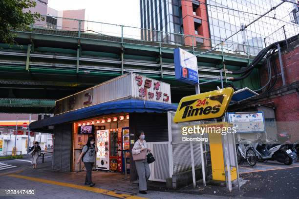 Pedestrians walk past vending machines near Akihabara station in Tokyo, Japan, on Thursday, Sept. 3, 2020. In Tokyo, the spaces beneath elevated...