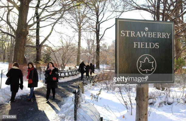 Pedestrians walk the path by the Strawberry Fields sign that leads to the Imagine tribute to former Beatle John Lennon December 8 2003 in Central...