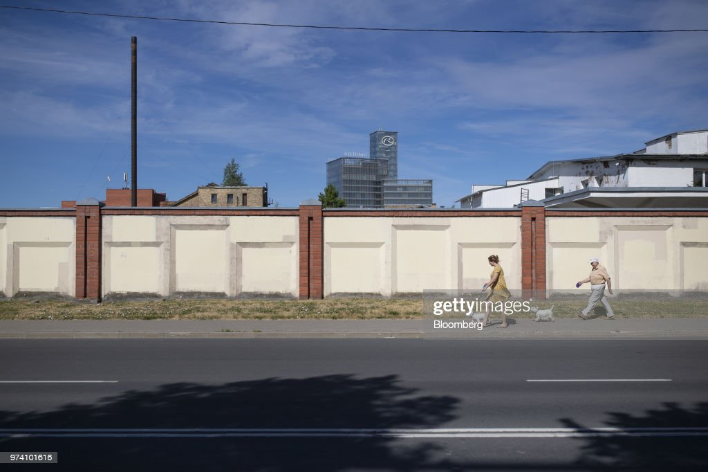 Pedestrians walk their dogs near the headquarters of Rietumu Banka AS in Riga, Latvia, on Wednesday, June 13, 2018. Latvia's plans to kick out risky cash from its scandal-plagued banks are about to accelerate. Photographer: Jasper Juinen/Bloomberg via Getty Images