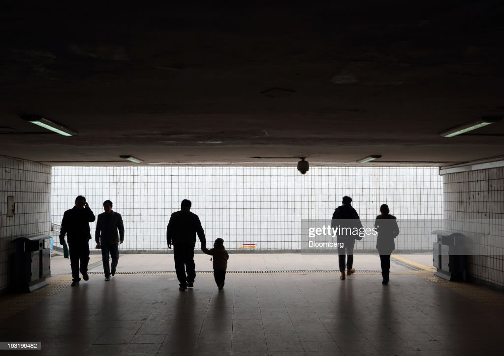 Pedestrians walk though an underground walkway in Beijing, China, on Wednesday, March 6, 2013. China maintained its economic-growth target at 7.5 percent for 2013 while setting a lower inflation goal of 3.5 percent, setting up a challenge for new leaders to keep prices in check without harming expansion. Photographer: Tomohiro Ohsumi/Bloomberg via Getty Images
