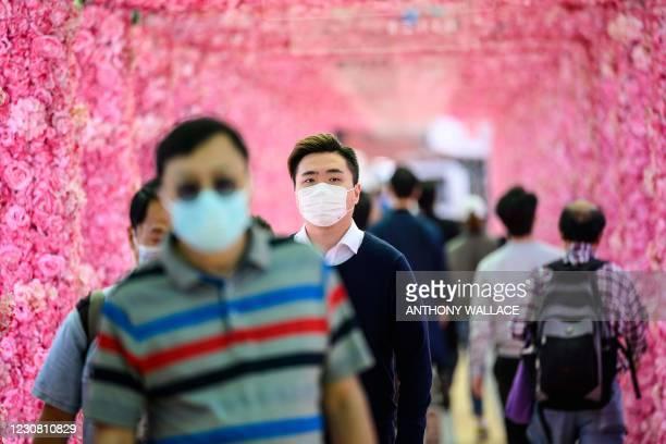 Pedestrians walk through a floral themed passageway in Hong Kong on January 27, 2021.