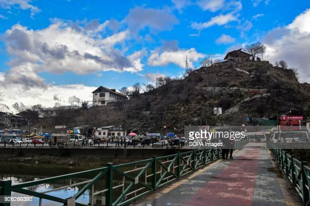 Pedestrians walk through a foot bridge on a partly cloudy day in Srinagar Indian administered Kashmir Ahead of prediction of rain and snow from...