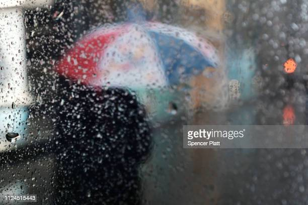 Pedestrians walk through a heavy late morning rain on January 24 2019 in New York City A flood watch has been issued for New York City as forecasts...