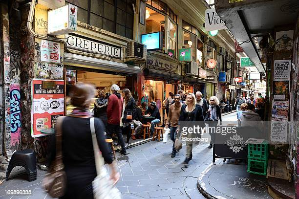 Pedestrians walk through a laneway lined with boutiques and street cafes in central Melbourne Australia on Sunday June 2 2013 The Australian Bureau...