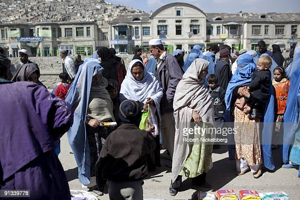 Pedestrians walk through a market area in the old city of Kabul Afghanistan March 4 2009 Kabul has an estimated population of 35 4 million people and...