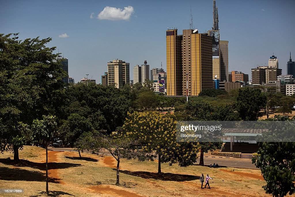Pedestrians walk through a public park beyond the city skyline in Nairobi, Kenya, on Friday, March 1, 2013. Next week's presidential vote will be the first since disputed elections in 2007 triggered ethnic fighting in which more than 1,100 people died and another 350,000 fled their homes. Photographer: Trevor Snapp/Bloomberg via Getty Images