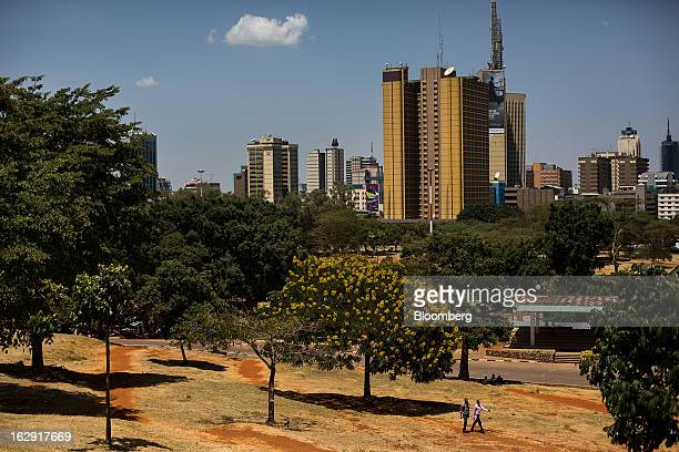 Pedestrians walk through a public park beyond the city skyline in Nairobi Kenya on Friday March 1 2013 Next week's presidential vote will be the...