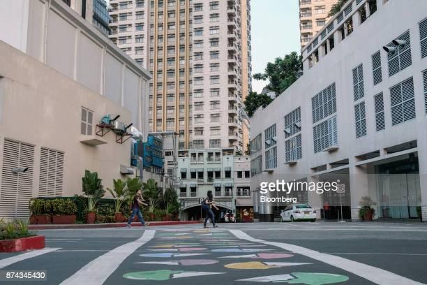 Pedestrians walk through a residential development in Quezon City Metro Manila Philippines on Tuesday Nov 14 2017 Economists are forecasting the...