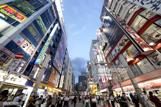 Pedestrians walk through a road as billboards on the facades of buildings and retail stores are illuminated at dusk in the Akihabara shopping...