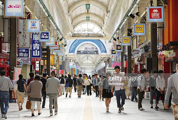 Pedestrians walk through a shopping street in Sapporo Hokkaido Prefecture Japan on Sunday June 9 2013 Japans economy grew more than the government...