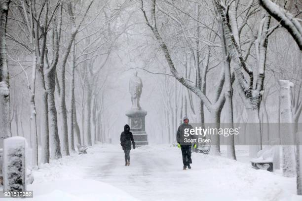 Pedestrians walk through a snow covered Commonwealth Avenue Mall as Winter Storm Skylar bears down on March 13 2018 in Boston Massachusetts This is...