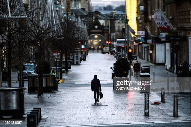 Pedestrians walk through central Glasgow as Britain enters a national lockdown in London on January 5, 2021. - Scotland is to impose a nationwide...