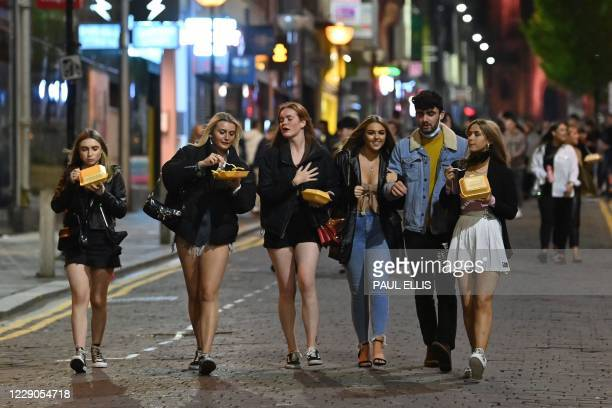 Pedestrians walk through central Liverpool, north west England on October 13 before fresh local lockdown are imposed to help stem a second wave of...
