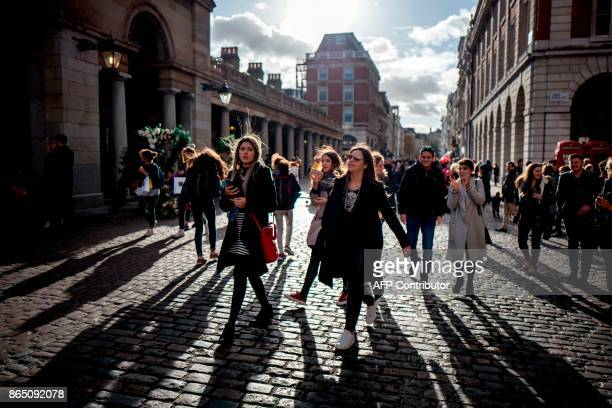 Pedestrians walk through Covent Garden in London on October 22 2017 Britain could be left poorer and weaker by Brexit and needing to spend more to...