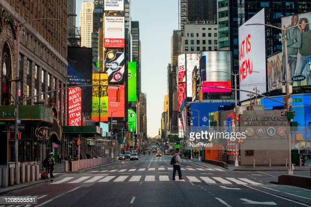 Pedestrians walk through en empty Times Square on Friday, March 2020 in New York, NY. The city officially announced the closure of all non-essential...