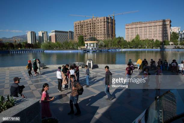 Pedestrians walk through Flagpole Park as cranes and buildings stand in the background in Dushanbe Tajikistan on Saturday April 21 2018 Flung into...