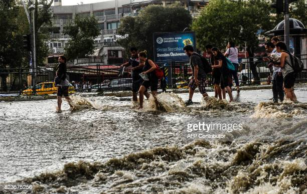 Pedestrians walk through floodwaters after a heavy downpour of rain and hail at Besiktas near Istanbul on July 27 2017 / AFP PHOTO / Bulent KILIC