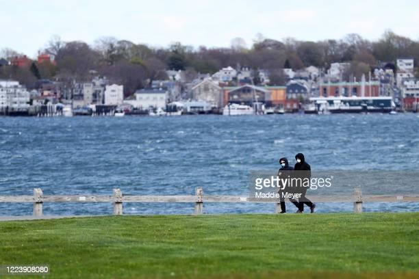 Pedestrians walk through Fort Adams State Park on May 09, 2020 in Newport, Rhode Island. Non-critical retail establishments began opening their doors...