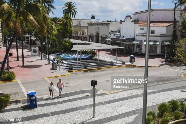 Pedestrians walk through Lincoln Road Mall in the South Beach neighborhood of Miami Beach, Florida, U.S., on Friday, March 20, 2020. Mayor Carlos...