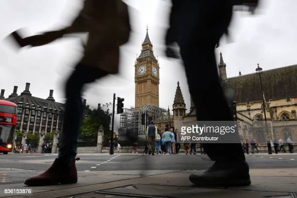 TOPSHOT Pedestrians walk through Parliament Square at the Houses of Parliament in London on August 21 2017 past Elizabeth Tower and Big Ben ahead of...