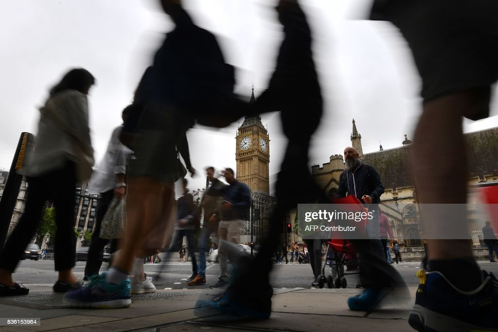 Pedestrians walk through Parliament Square at the Houses of Parliament in London on August 21, 2017 past Elizabeth Tower and Big Ben ahead of the final chimes of the famous bell before renovation works begin. Britain's Big Ben bell fell silent on August 21 for four years of renovation work, with its final 12 bongs ringing for midday in front of a crowd of over a thousand people. The repair work on the landmark looming over the Houses of Parliament in Westminster has sparked protests including from Prime Minister Theresa May. STANSALL