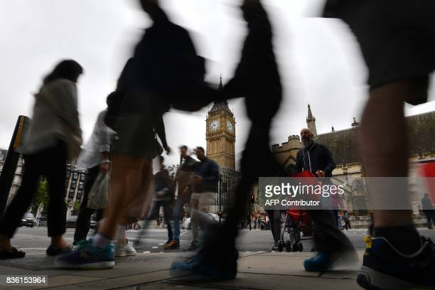 Pedestrians walk through Parliament Square at the Houses of Parliament in London on August 21 2017 past Elizabeth Tower and Big Ben ahead of the...