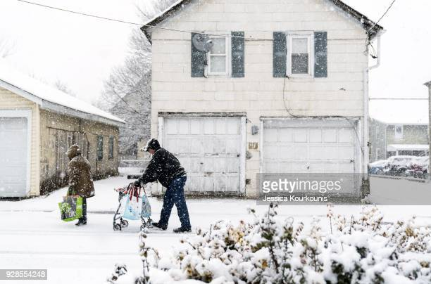 Pedestrians walk through snow on March 7 2018 in Quakertown Pennsylvania This is the second nor'easter to hit the Northeast within a week and is...