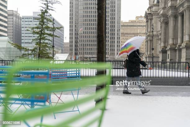 Pedestrians walk through snow sleet and high winds on March 21 2018 in Philadelphia Pennsylvania The fourth nor'easter in three weeks has forced...