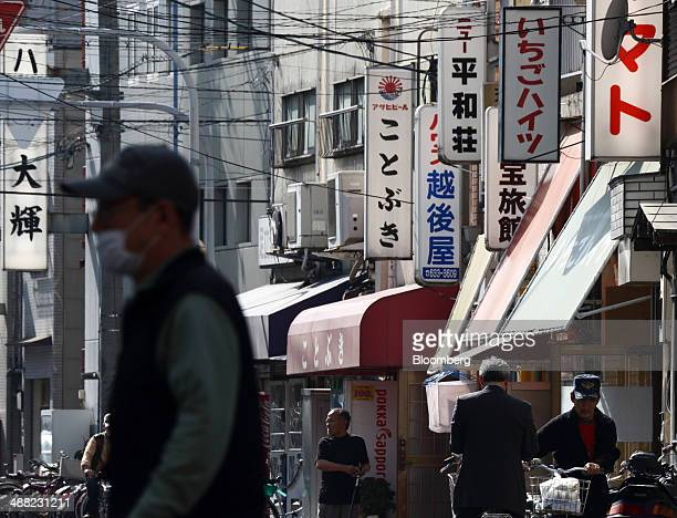 Pedestrians walk through the Airin area of Nishinari ward in Osaka Japan on Friday May 2 2014 Osaka prefecture's economic output dropped 62 percent...