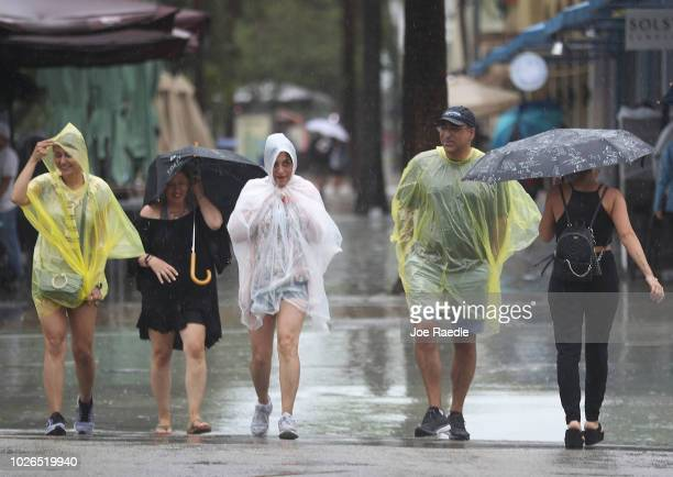 Pedestrians walk through the rain from Tropical Storm Gordon on September 3, 2018 in Miami Beach, Florida. Tropical Storm Gordon is heading into the...