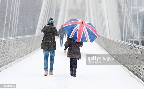 Pedestrians walk through the snow as they cross the Jubilee bridge in central London on January 18 2013 Snow swept across Britain on Friday forcing...