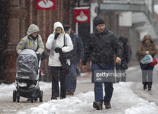 Pedestrians walk through the snow in Belfast City centre in Northern Ireland on March 22 2013 Britain should be celebrating the start of spring but...