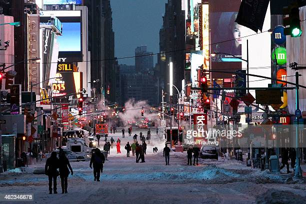 Pedestrians walk through Times Square on the morning of January 27 2015 in New York City New York and much of the Northeast was hit with heavy...