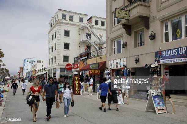 Pedestrians walk through Venice Beach in Los Angeles, California, U.S., on Friday, June 26, 2020. California reported 5,349 new cases, its...