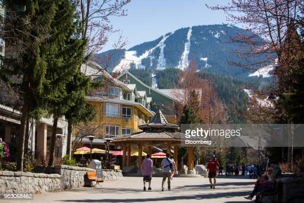 Pedestrians walk through Whistler Village in front of Vail Resorts Inc Whistler Blackcomb ski mountain in Whistler British Columbia Canada on Friday...