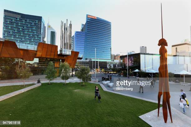 Pedestrians walk through Yagan Square as the Bankwest Tower center stands in the central business district of Perth Australia on Wednesday April 11...