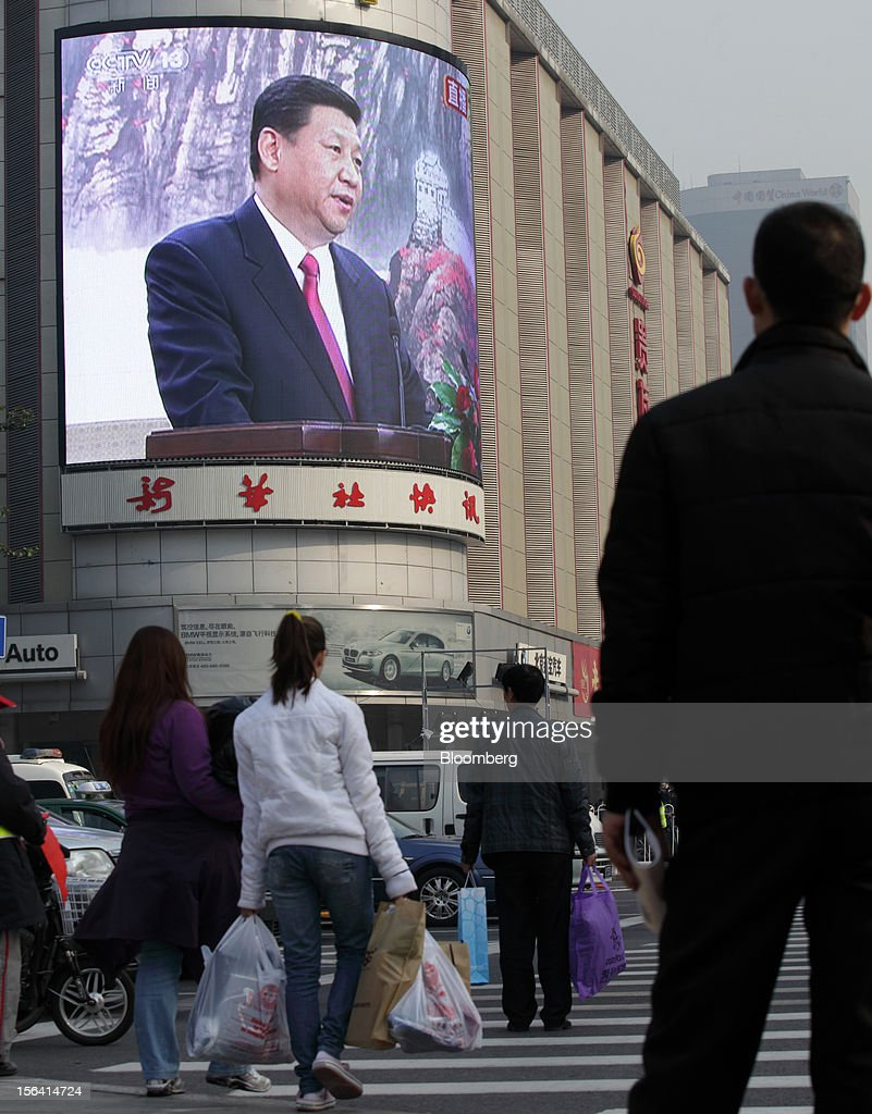 Pedestrians walk toward a monitor broadcasting a news conference by Xi Jinping, general secretary of the Communist Party of China, outside a subway station in Beijing, China, on Thursday, Nov. 15, 2012. Xi replaced Hu Jintao as head of the Chinese Communist Party and the nation's military, ushering in the fifth generation of leaders who are set to run the world's second-biggest economy over the next decade. Photographer: Tomohiro Ohsumi/Bloomberg via Getty Images