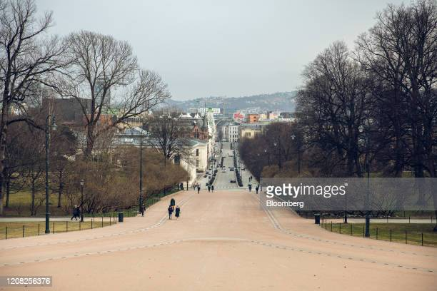 Pedestrians walk towards the Royal Palace in Oslo Norway on Wednesday March 25 2020 Norway will extend drastic measures imposed to limit the spread...