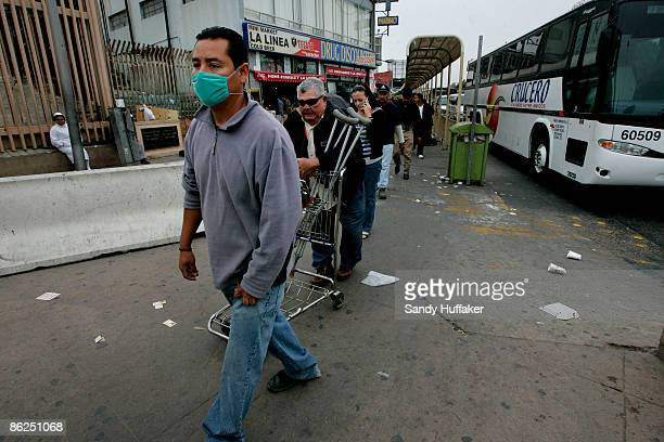 Pedestrians walk towards the United States-Mexico border while some wear surgical masks at the Port of Entry on April 27, 2009 in Tijuana, Mexico....