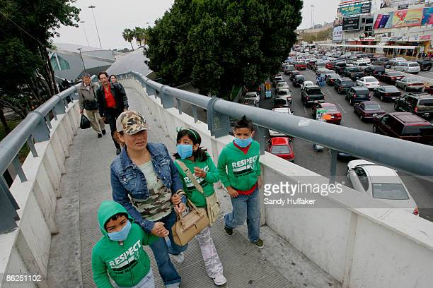 Pedestrians walk towards the United StatesMexico border while wearing surgical masks on April 27 2009 in Tijuana Mexico US Health officials advises...