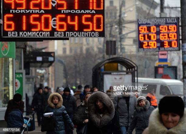 Pedestrians walk under a board listing foreign currency rates against the Russian ruble outside an exchange office in central Moscow on December 1...