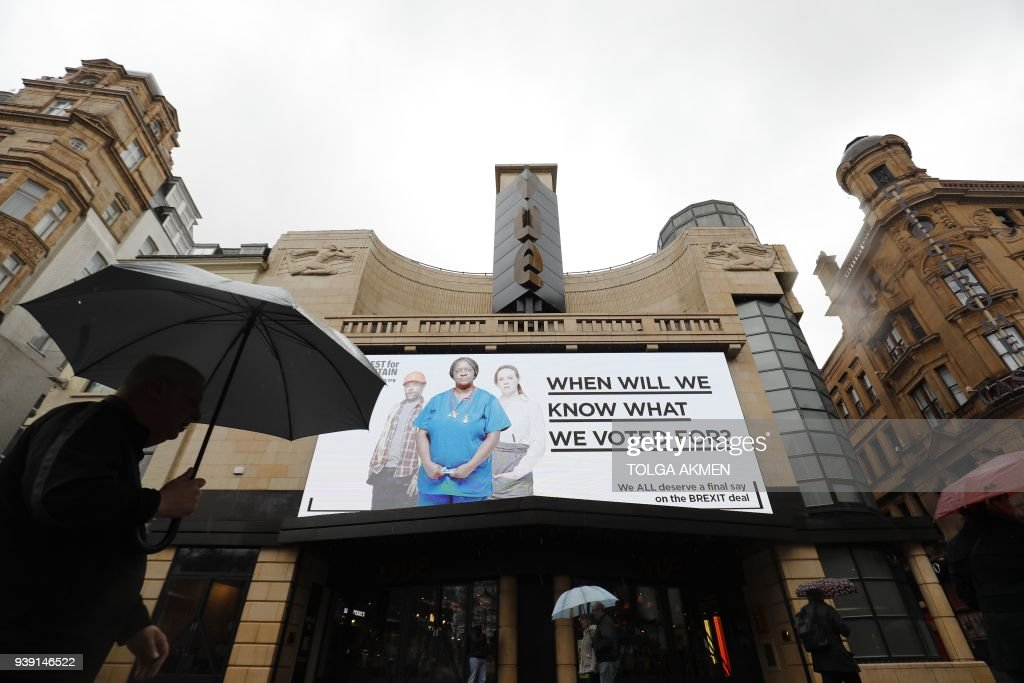Pedestrians walk under a new billboard launched by campaign group Best for Britain in Leicester Square in London on March 28, 2018. Campaign group Best for Britain launched a media campaign on March 28 ahead of the anniversary of the invocation of Article 50 calling for a public vote on the Brexit deal. PHOTO / Tolga AKMEN