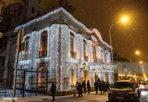Pedestrians walk under the snow in front of the famous restaurant 'Café Pushkin' decorated with festive lights for the upcoming holidays in Moscow on...