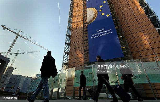 Pedestrians walk underneath a giant euro banner featuring an image of a euro coin and promoting stronger European economic governance as it hangs on...
