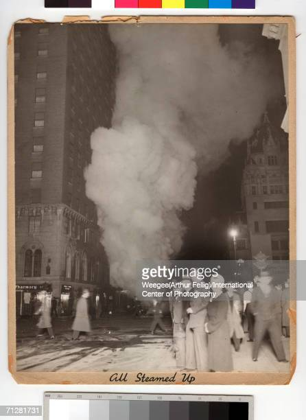 Pedestrians walk up and down Seventh Avenue as a cloud of smoke rises from a fire down the block, New York, New York, early 1940s. Weegee entitled...